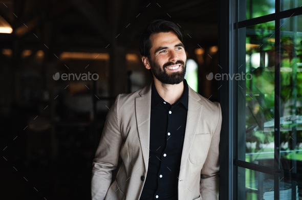 Portrait of businessman with jacket standing indoors in restaurant - Stock Photo - Images