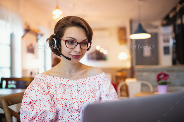 Young woman with headset and laptop indoors in cafe, working - Stock Photo - Images