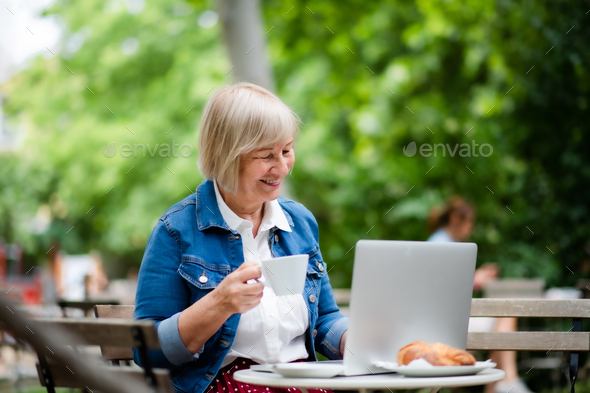 Senior woman with coffee sitting outdoors in cafe, using laptop - Stock Photo - Images