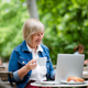 Senior woman with coffee sitting outdoors in cafe, using laptop - PhotoDune Item for Sale