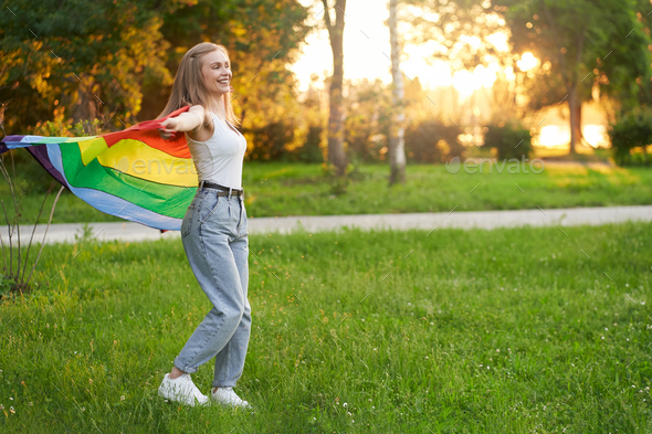 Laughing tolerant woman dancing with rainbow lgbt flag - Stock Photo - Images