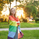Smiling woman holding rainbow flag on shoulders - PhotoDune Item for Sale