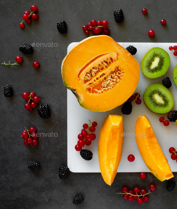 top view cutting board with fresh fruit on dark gray background with cold water drops - Stock Photo - Images