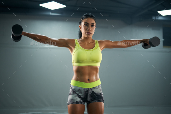 Female bodybuilder training with dumbbells - Stock Photo - Images