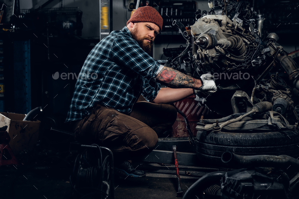 Bearded male repairing car's engine in a garage. - Stock Photo - Images
