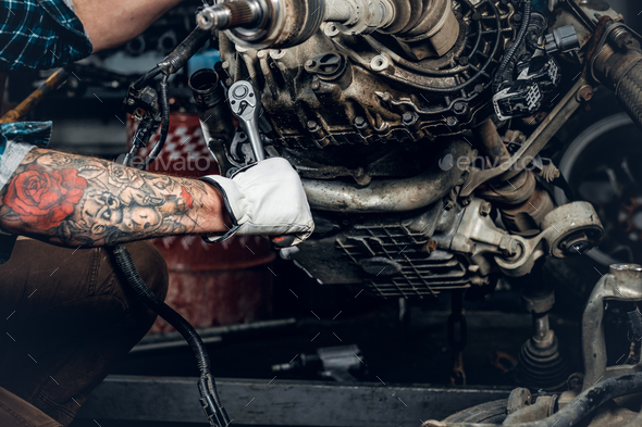 bearded male repairing engine of a car in a garage. - Stock Photo - Images