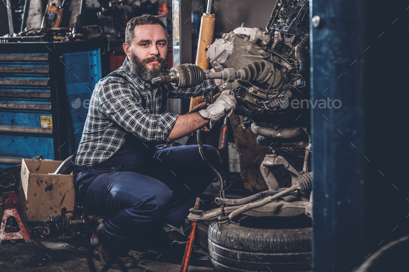 A man repairing the car's engine. - Stock Photo - Images