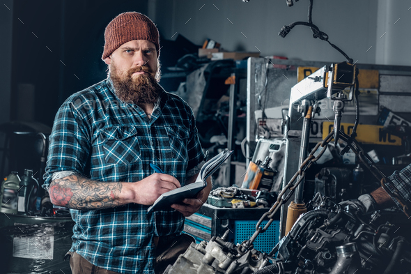 Mechanicl inspecting engine of a car in a garage. - Stock Photo - Images