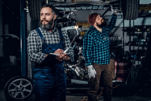 Two mechanics in a garage. - Stock Photo - Images