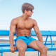 Sexy muscular man in a blue shorts and sunglasses. - PhotoDune Item for Sale
