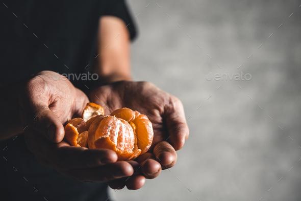 Ripe juicy sweet orange mandarins in a human hand against a dark background. PNOV2019 - Stock Photo - Images