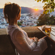 Young woman siting with glass of beer looking at sunset over city Graz in Austria - PhotoDune Item for Sale