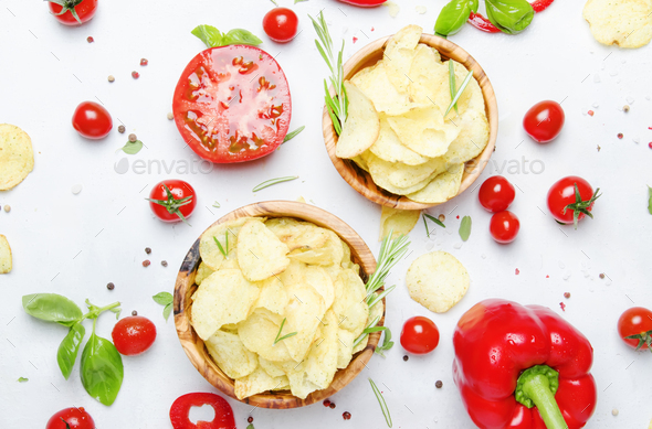 Unhealthy food background, potato chips with salt, tomatoes, chili and bell pepper - Stock Photo - Images