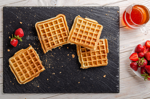 Homemade Belgian waffles on slate tray with maple syrup and strawberries aside. Flat lay view - Stock Photo - Images