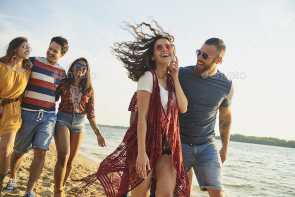 Happy friends walking on the beach. - Stock Photo - Images