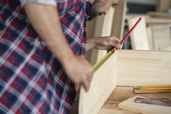 Back view of carpenter measuring wooden plank - Stock Photo - Images