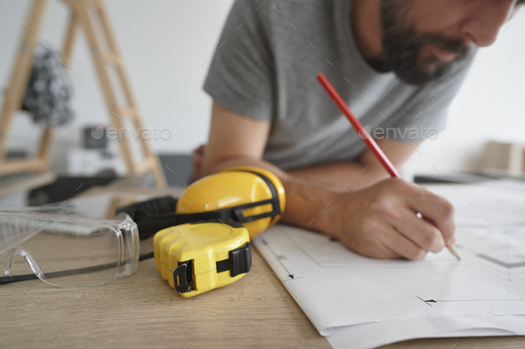 Carpenter making corrections to plans - Stock Photo - Images