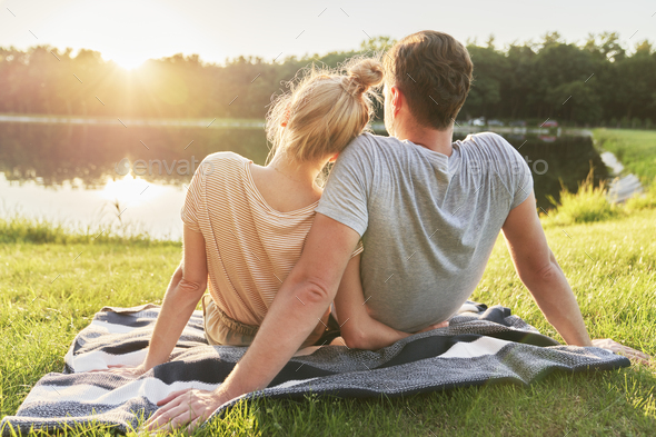 Couple watching sunset by the lake - Stock Photo - Images