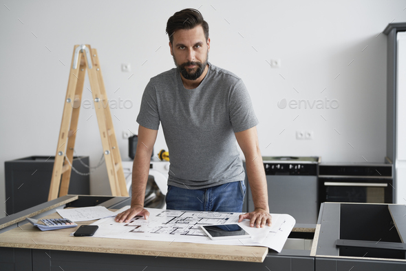 Portrait of  carpenter while installing kitchen furniture - Stock Photo - Images