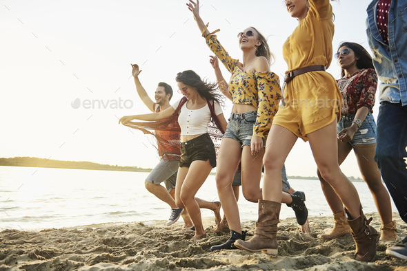 Happy friends running on beach at sunset - Stock Photo - Images