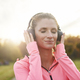 Female athlete with headphones listening to music outdoors - PhotoDune Item for Sale
