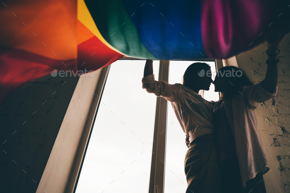 Lesbian couple in silhouette in love standing near the window with the rainbow flag. - Stock Photo - Images