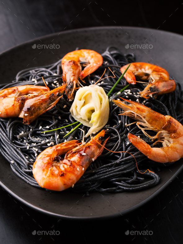Black spaghetti with shrimps, ginger and sesame seeds - Stock Photo - Images