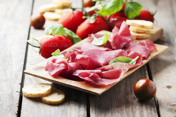 Appetizer with italian bresaola and tomato - Stock Photo - Images