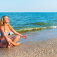 Woman in yoga pose sitting by sea - PhotoDune Item for Sale