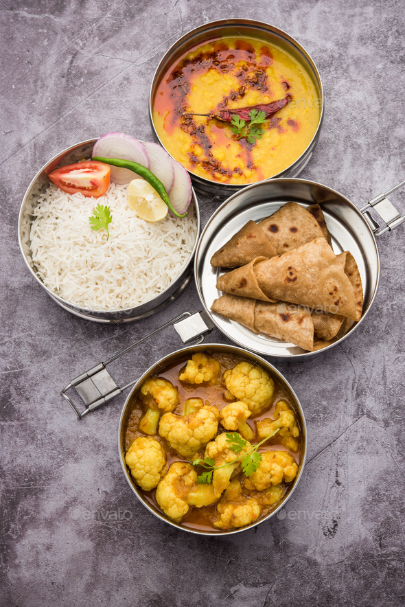 Indian Lunchbox or Tiffin includes Cauliflower Masala, Dal Fry, Rice, Chapati and salad - Stock Photo - Images