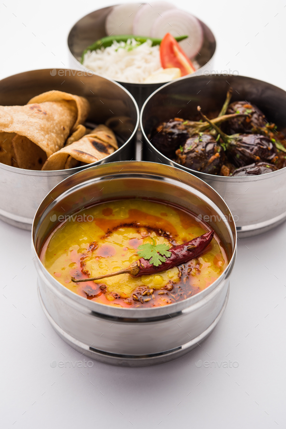 Indian Veg Lunchbox for office of workplace with Baingan Masala, dal fry rice and chapati - Stock Photo - Images