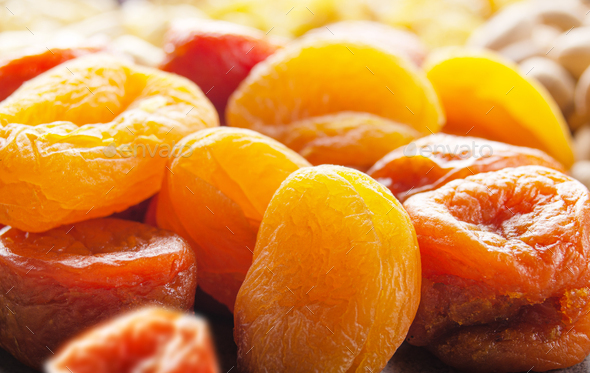 Pile of dried apricots on kitchen table. Healthy nutritious natural food - Stock Photo - Images