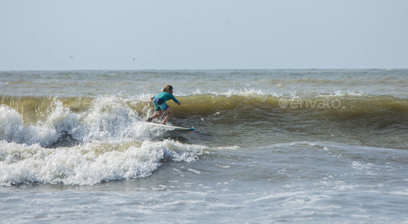 Panorama of young boy surfing on the Atlantic Ocean. - Stock Photo - Images