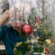 Man putting up Christmas decoration at home holding a red bauble in his hand - PhotoDune Item for Sale