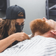 A man at a barbershop. Woman barber clipping beard and mustache. Barber woman in mask. - PhotoDune Item for Sale