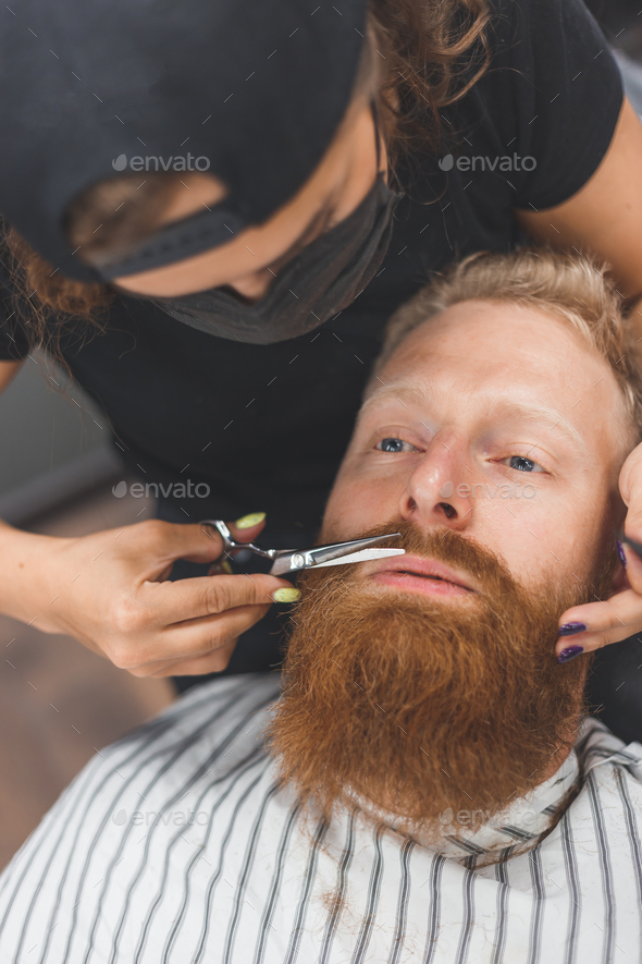 A man at a barbershop. Woman barber clipping mustache. Barber woman in mask. - Stock Photo - Images