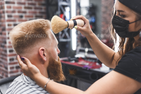 The hairdresser cleans the face of a young guy with a brush after a haircut - Stock Photo - Images