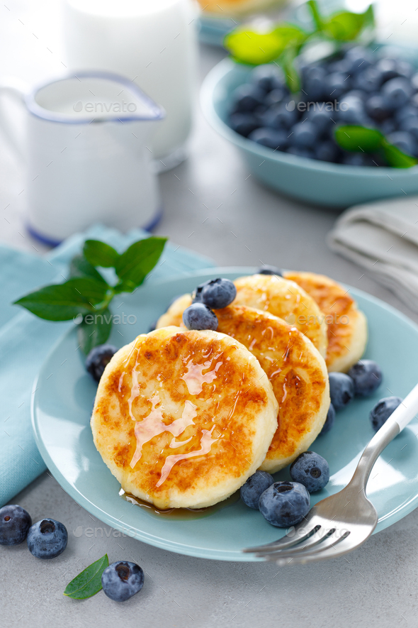 Cottage cheese pancakes, sweet curd fritters with berries, syrniki with honey and fresh blueberry - Stock Photo - Images