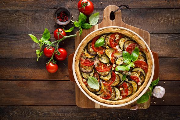 Tart with vegetables. Homemade savory tart with eggplant, zucchini, tomatoes, garlic, mozzarella - Stock Photo - Images