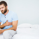 Young man having chest pain on bed - PhotoDune Item for Sale