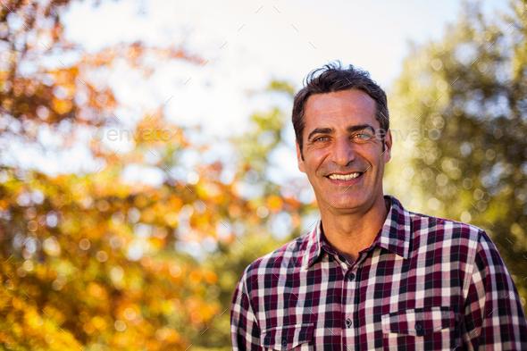 Portrait of happy man at park - Stock Photo - Images