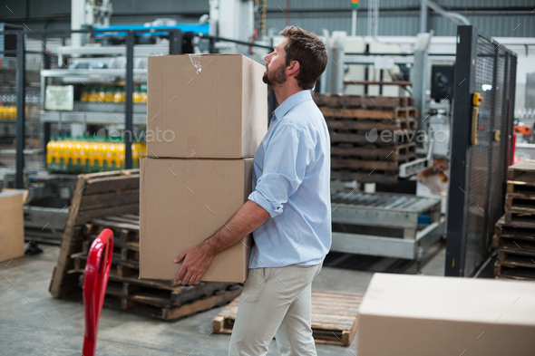 Factory worker carrying cardboard boxes in factory - Stock Photo - Images