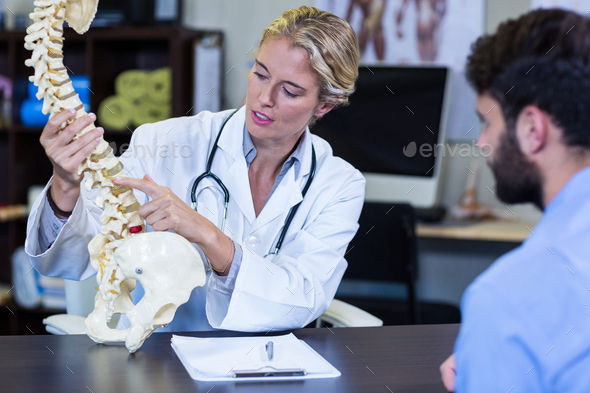 Physiotherapist explaining spine model to patient - Stock Photo - Images