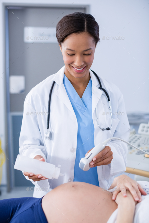 Doctor doing ultrasound scan for pregnant woman - Stock Photo - Images