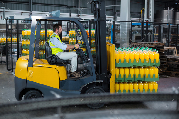 Factory worker loading packed juice bottles on forklift - Stock Photo - Images