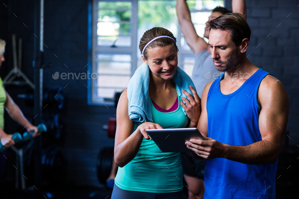 Athletes looking in tablet computer at gym - Stock Photo - Images