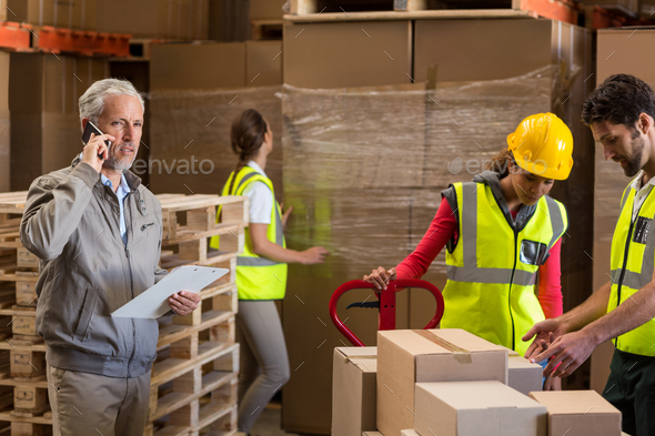 Warehouse manager and workers preparing a shipment - Stock Photo - Images