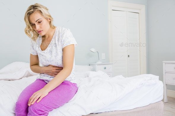 Young woman having stomach pain in bed - Stock Photo - Images