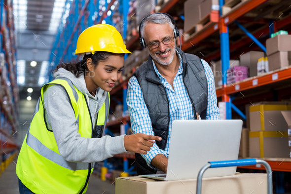 Warehouse manager and female worker using laptop - Stock Photo - Images