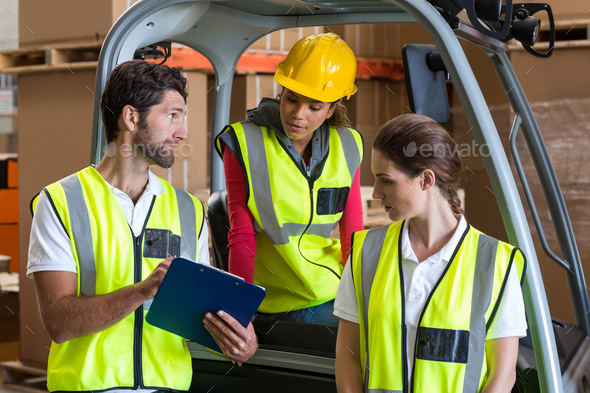 Warehouse workers talking with forklift driver - Stock Photo - Images